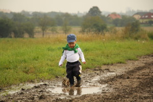 a little boy likes to run and jump in a puddle